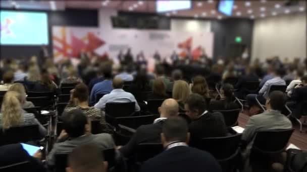 Skupina lidí poslouchá reproduktor na konferenci. Podnikatelé na konferenci