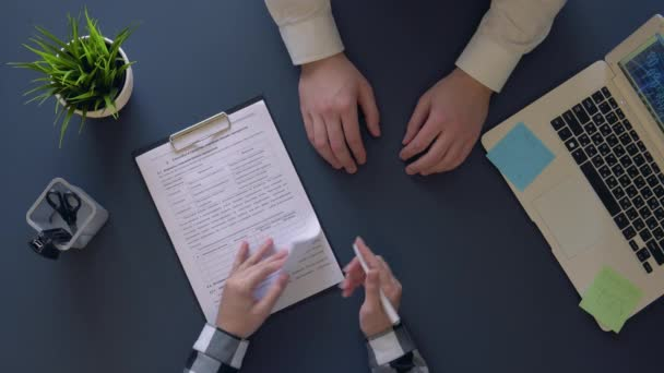 business man signs a contract while sitting at the table and shakes hands with a partner. overhead shot