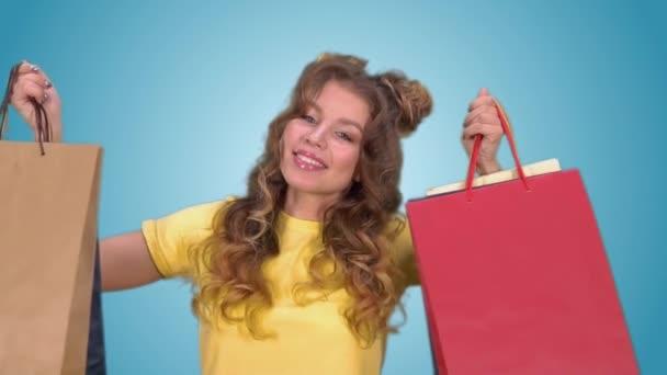 Boldog, fiatal lány, több színű bevásárló táska tartó, és mosolyogva