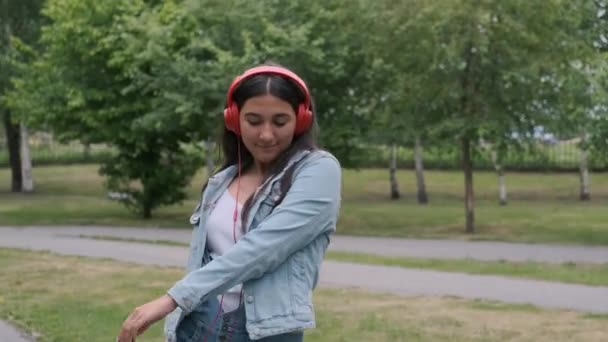 beautiful cheerful girl dancing in the park listening to music on headphones. Fun mood