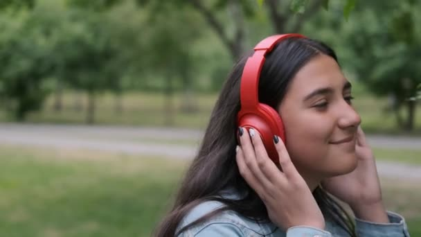happy girl dancing in the park near the trees listening to cheerful music in headphones. Fun mood. Close-up