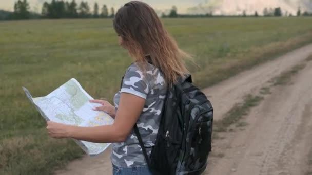 Krásná žena, turistka s batohu a s mapou v ruce, stojí na pozadí hor. Otáčení kamery kolem