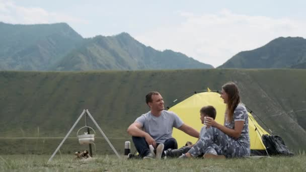Happy family with a child laughing on campsite near a tent with a bonfire.
