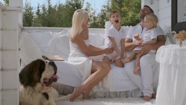 Šťastná rodinka s dětmi a pes se baví ukazovat gestikulky, když sedí na verandě u dámy. Teplé rodinné vztahy
