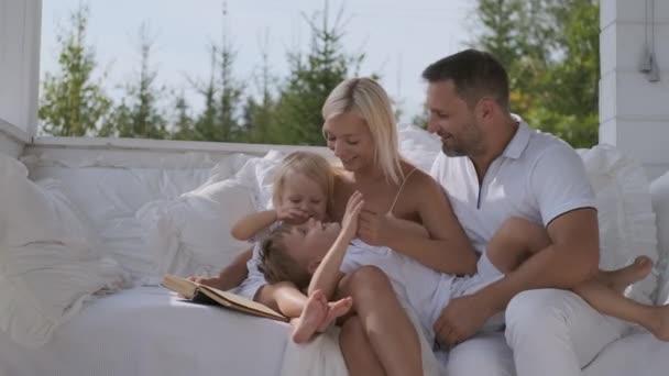 Mladá šťastná rodinka matka a dva synové, kteří se baví sedět na zářivé verandě u domu