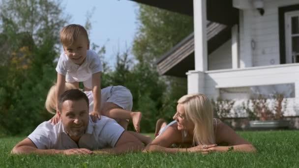 Mladá rodinka matka a dva synové se baví ležet na trávě blízko domu