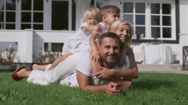 Šťastná rodina s dětmi, kteří se baví na sobě u domu na trávě