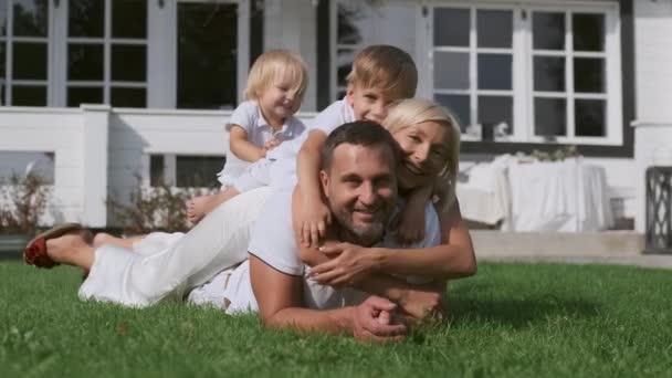 Šťastná rodina s dětmi, kteří si na sobě leží u domu v trávě. Posunutí kamery doprava