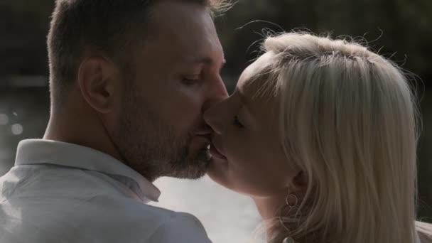 Szerető szép pár csók ülve egy mólón a folyó közelében. Közeli
