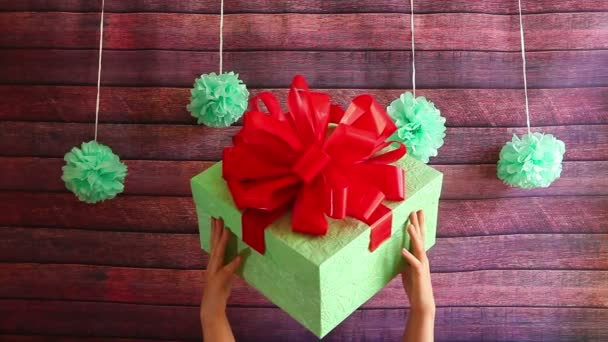 Ruce drží krásná Dárková krabice s červenou stužkou, všechno nejlepší k narozeninám nebo novoroční svátky koncept atd