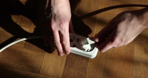 Male Hand Plugging White Power Plug Into White Multiple Socket Indoors In Slow Motion. Electricity Concept