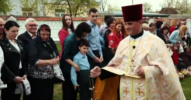 KAMENKA-BUZKA, UKRAINE, APRIL 2019: Priest goes at people and waving a censer thus making a pleasant smell around and creating a small smoke. Passover feast