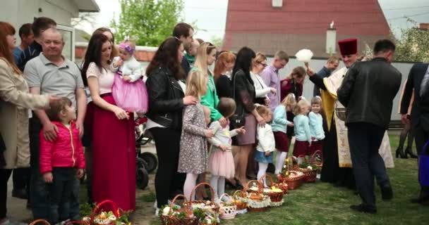 KAMENKA-BUZKA, UKRAINE - April 27, 2019: Traditional Orthodox Easter ritual of priest blessing Easter cakes and eggs