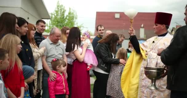 KAMENKA-BUZKA, UKRAINE - April 27, 2019: Priest consecrates Easter baskets with food. Christians near the temple. Traditions of celebration of Easter in Ukraine