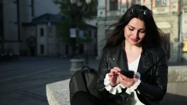 loseup of beautiful young business Caucasian woman with smartphone texting messenger sits near the monument. Slow motion. Prores