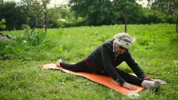 alte Frau mit Sonnenbrille sitzt auf Yogamatte auf Längsspalten