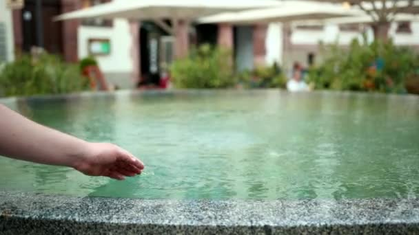 the hand of the young guy dives into the fountain, from which water flows