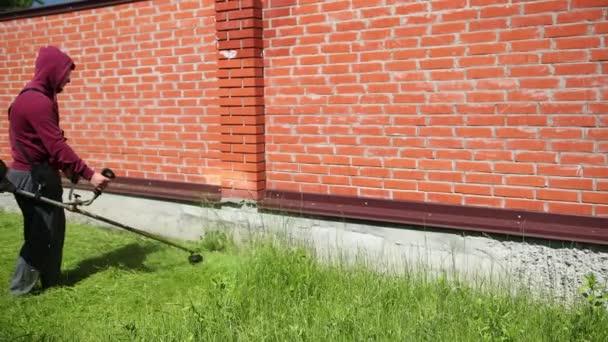 Mann mit Schutzbrille mäht hohen Rasenmäher an einem hohen Ziegelzaun entlang