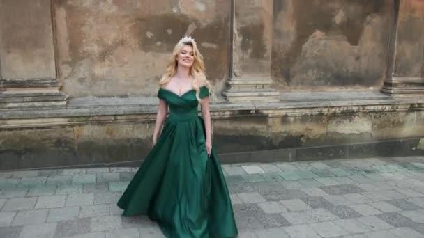 dívka v zelených šatech s holýma rameny, s korunou, která se nachází blízko staré budovy