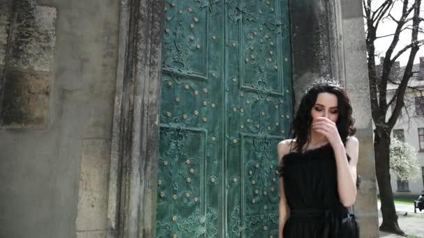 schlankes Mädchen, brünett, im schwarzen Kleid, mit Krone, posierend, in der Nähe eines alten Gebäudes