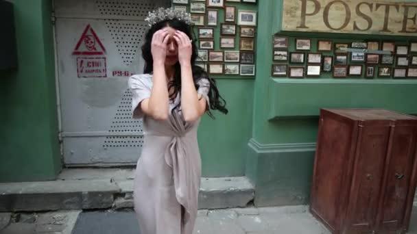 brünette Miss, in grauem Kleid, schlanken Beinen, hellem Make-up, Krone auf dem Kopf, posiert