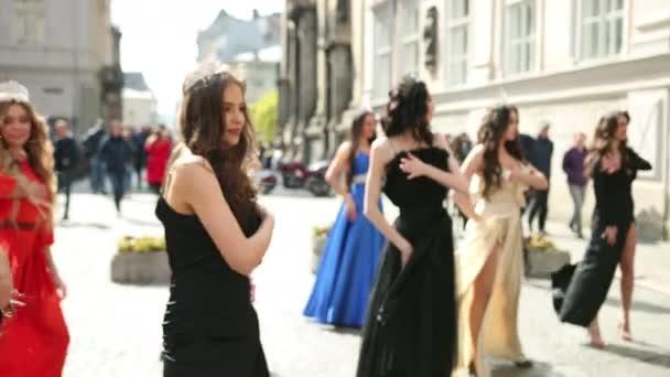 sok gyönyörű lányok öltözött ruhák és koronák táncoló az utcán