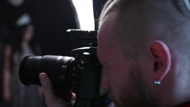 man photographer takes pictures with a professional camera, in the studio