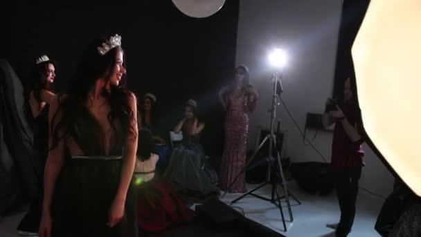 Fotograf fotografiert Mädchen Modell, brünett, in einem grauen Kleid, im Studio