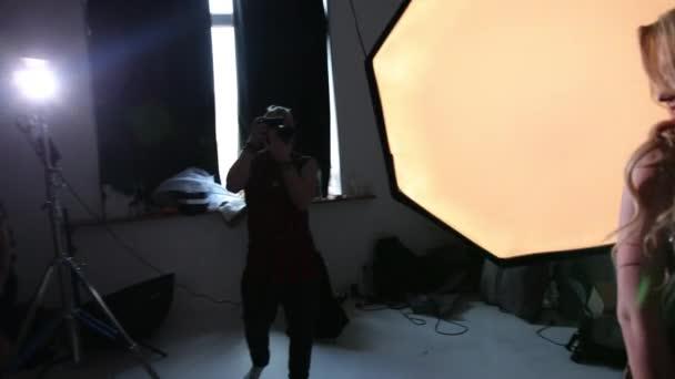 Fotograf fotografiert ein Model, blond, in einem schönen Kleid, im Studio