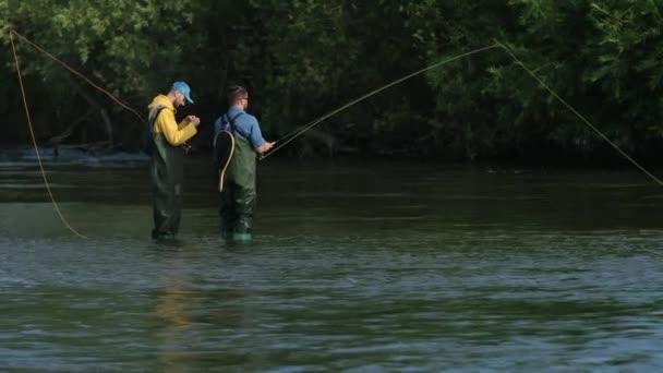 Horgászat, két férfi halászat a folyón, állva a vízben, egy kis áram