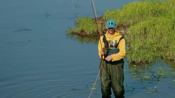 Muž, který drží rybářský prut, hází plovák, rybařit v řece