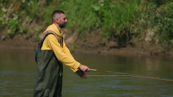 férfi Halász dob egy úszó, a halászat a folyón, állva a vízben