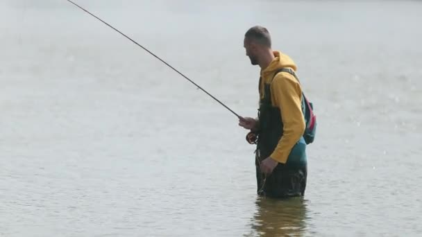 člověk rybář, hází plovák, vytahuje ryby z řeky stojící ve vodě