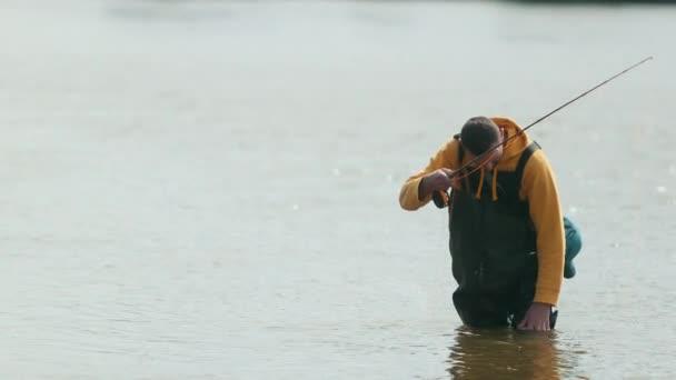 Rybaření, člověče rybář, hází plovák, vytahuje ryby z řeky