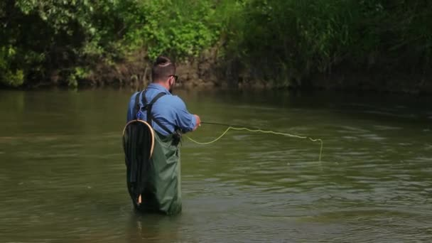 Halász dob egy úszó, egy férfi halászat a folyón, állva a vízben