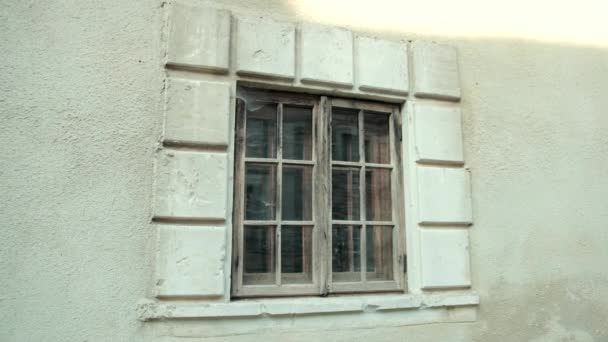 old wooden window, on a gray shabby building, around cobwebs and dirt