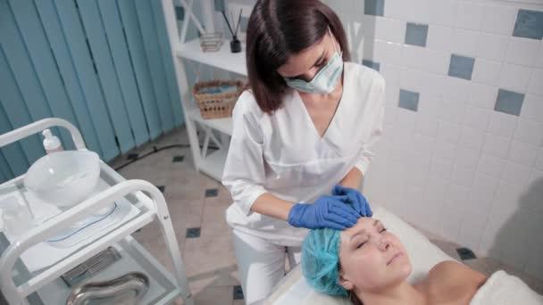 ápolónő orvos a kék kesztyű, tesz egy nő arc masszázs könnyű mozgások