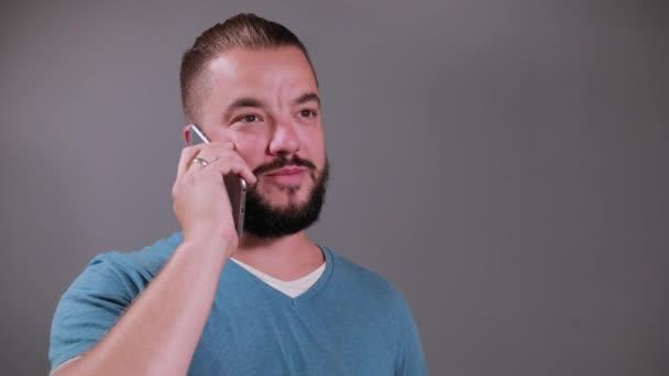 Fiatal férfi gazdaság okostelefon felett szürke elszigetelt háttér beszélni telefonon