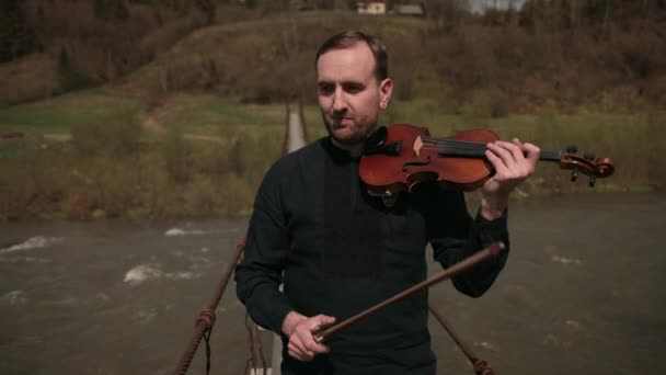 Violinist on the bridge, street Performer playing violin, outside. swift river