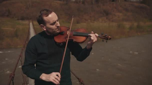 Hegedűs a hídon, utcai hegedűs, kint. gyors folyó