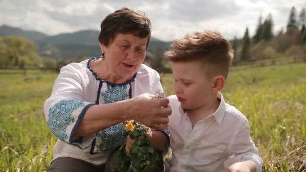 Babička dělá věnec z divokých květin se svým mladým vnukem. Relaxovat venku