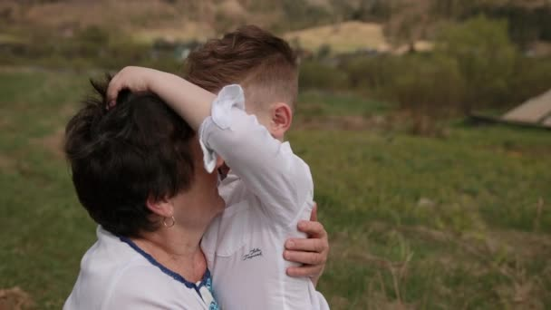 Vnuk se blíží k babičce. Položil jí ruku kolem krku. láska babi