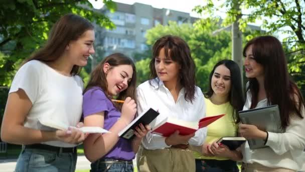 Egy portré fiatal diákokról, akik könyveket tartanak az utcán. Csoport boldog végzős státusz