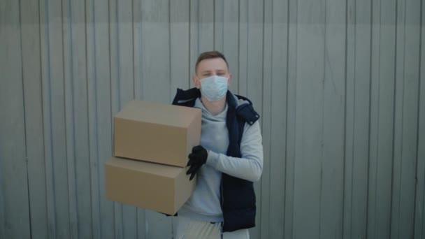 Zusteller mit Schutzmaske trägt Kisten in der Hand