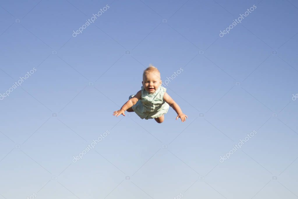 Flying child with a happy face against the blue sky. Concept game with children, happy family.