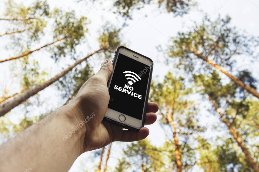 Male hand is holding a phone with sign no service  above his head against the background of trees in a pine forest. Concept of no service, wifi, internet in the forest or a place far from the city