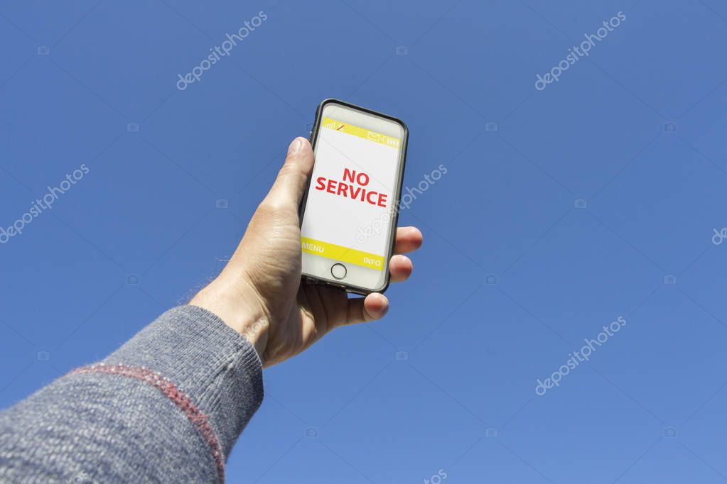 Man's hand is holding a phone and trying to find a connection against the blue sky. On the phone screen, the symbol with no signal