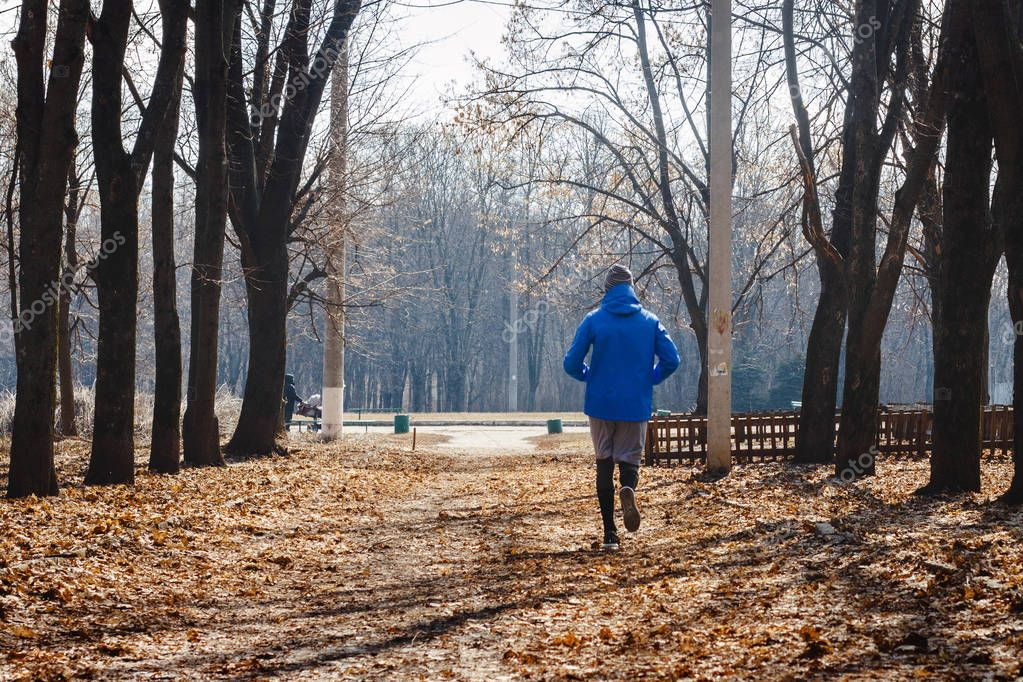 A man in a blue jacket makes a run in an autumn or spring park. Jogging concept, workout outdoor.