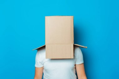 Young man in a white T-shirt with a cardboard box on his head on a blue background.