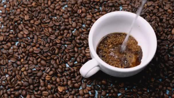 Americká káva se vaří s vroucí vodou v bílém hrnci na pozadí kávových bobů